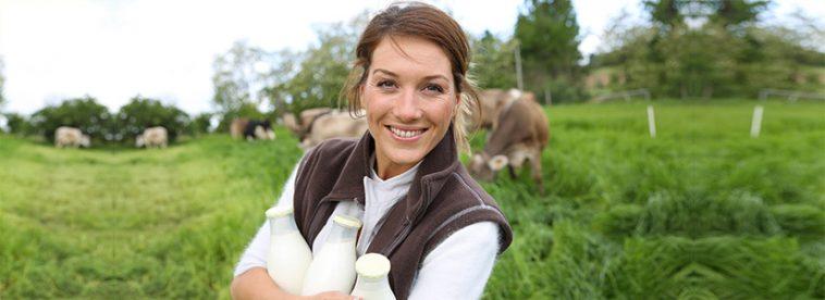Bäuerin mit Milchflaschen vor weidenden Kühen