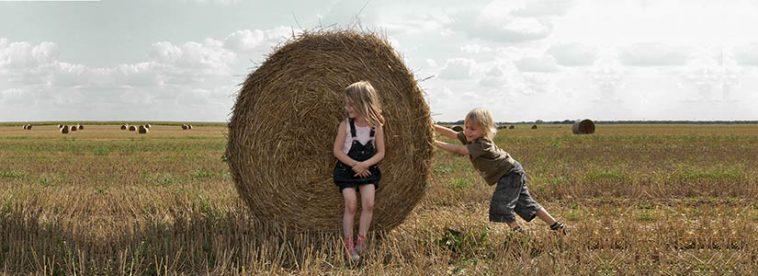 Kinder mit Strohballen am Feld.