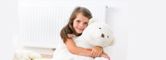 Mädchen mit Teddy vor Heizkörper