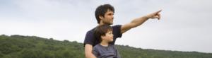 Vater und Kind sitzen am Strohballen