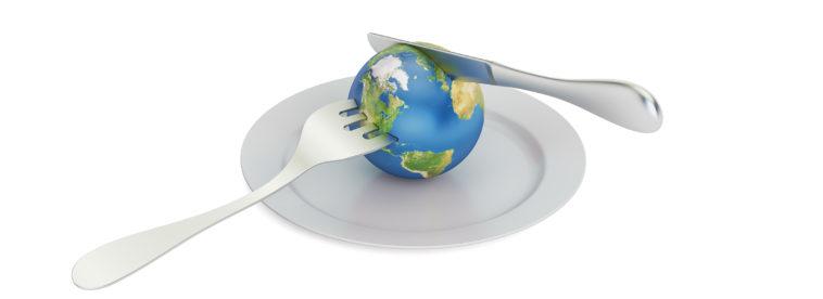 Erdkugel mit Messer und Gabel auf einem Teller