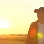 Junge Frau mit einem Tablett auf einem Weizenfeld